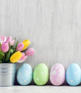 wielkanocni-jajka-i-wiosna-bukiet-tulipany-na-drewnianym-stole-87194082